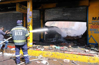 FILE - A shopkeeper watches as a fireman douses down a burned and damaged property after overnight unrest and looting in Alexandra township, Johannesburg, South Africa, Sept. 3, 2019.