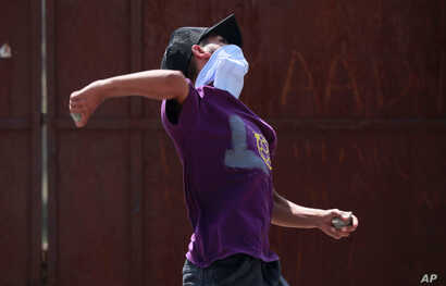 A protester throws a stone towards Indian police during a protest after the funeral of Asrar Ahmed Khan, who recently died after being injured during a protest on Aug. 6, 2019, in Srinagar, Sept. 4, 2019.