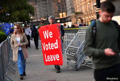 A pro-Brexit protester carries signs outside the Houses of Parliament in London, Sept. 4, 2019.