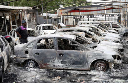 A man looks at cars that were burned during the latest spate of xenophobic attacks, at a car dealership in Johannesburg, South Africa, Sept. 5, 2019.