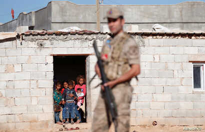 FILE - Locals look on as a Turkish soldier stands guard in a border village on the Turkish-Syrian border near Akcakale in Sanliurfa province, Turkey, Sept. 8, 2019.
