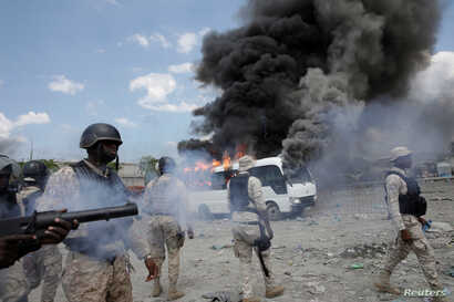 Haitian National Police (PNH) officers stand next to a burning police bus during a protest outside the facilities of the Parliament and the Senate in Port-au-Prince, Haiti, September 11, 2019.
