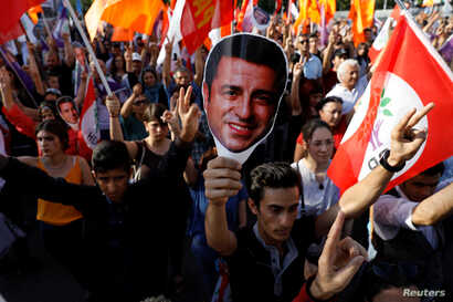 FILE - Supporters of Turkey's main pro-Kurdish Peoples' Democratic Party (HDP) hold masks of their jailed former leader Selahattin Demirtas during a rally in Ankara, Turkey, June 19, 2018.