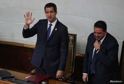 Venezuelan opposition leader Juan Guaido waves next to Stalin Gonzalez, second Vice President of the National Assembly, as they attend a session of the National Assembly in Caracas, Sept. 24, 2019.