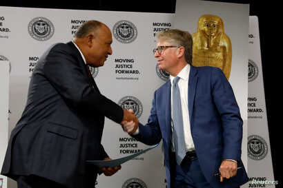 Egypt's Foreign Minister Sameh Shoukry and Manhattan District Attorney Cyrus R. Vance Jr. greet each other during a news conference to announce the return of the gold coffin of Nedjemankh to the people of Egypt, in New York City, Sept. 25, 2019.