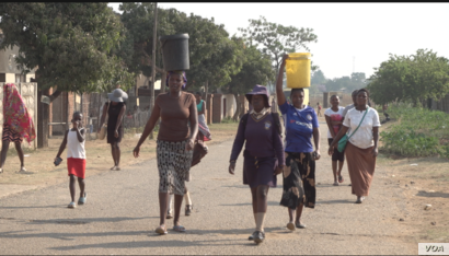 Women carry buckets of water from an open well, in Harare, Sept. 23, 2019. (C.Mavhunga/VOA)