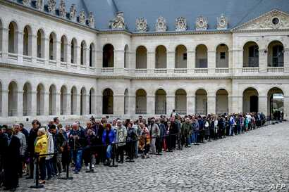 People queue to say a final farewell to former French President Jacques Chirac as the coffin lie in state at the Saint-Louis-des-Invalides cathedral at the Invalides memorial complex in central Paris, Sept. 29, 2019.
