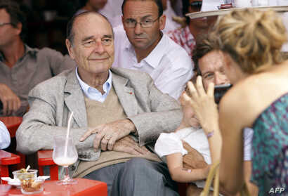 FILE -  France's former President Jacques Chirac poses as a womans takes a picture of him sitting at a table outside the famous Le Senequier cafe in the French Riviera sea resort of Saint-Tropez, Aug. 14, 2011.