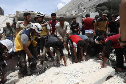 FILE - Syrian rescue teams and civilians search for survivors amid rubble in a bombarded area following a reported airstrike by regime forces and their allies on the market town of Kfar Ruma in Syria's northwestern Idlib province, May 30, 2019.