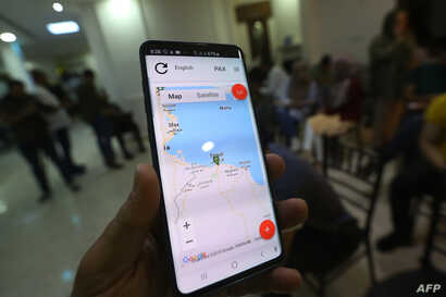 "A journalist shows application ""Kon Chahed"" (Be a witness), which aims to protect reporters by providing them with a safe way to document attacks, at the Libyan Center for Freedom of Press (LCFP) in Tripoli,  Aug. 14, 2019."