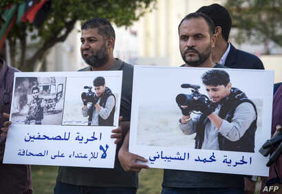 Libyan journalists hold placards bearing the portraits of Mohamad al-Gurj and Mohamad al-Shibani, who were detained and their fate remains unknown, during a protest in the capital Tripoli,  May 5, 2019.