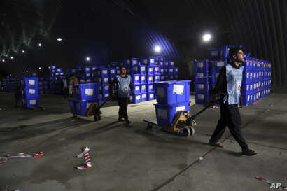 Afghan election workers transport ballot boxes for distribution ahead of presidential elections, at the Independent Election Commission compound, in Kabul, Afghanistan, Sept. 23, 2019.