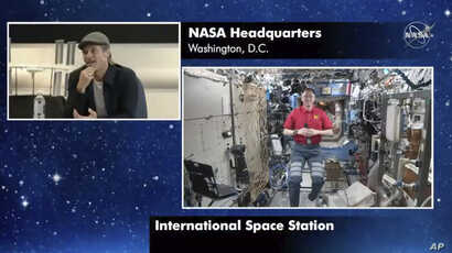 "In this image taken from NASA video actor Brad Pitt, left, star of the new space movie ""Ad Astra,"" speaks from NASA headquarters in Washington, to astronaut Nick Hague abroad the International Space Station, Sept. 16, 2019."