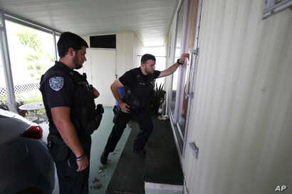 Vero Beach police officers James Doty and Chayse Hatfield, left, knock on doors to notify residents of a trailer park community of a mandatory evacuation, in preparation for Hurricane Dorian, in Vero Beach, Fla., Sept. 2, 2019.