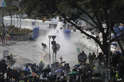 Anti-government protesters are sprayed by water cannon during a demonstration near Central Government Complex in Hong Kong, Sept. 15, 2019.