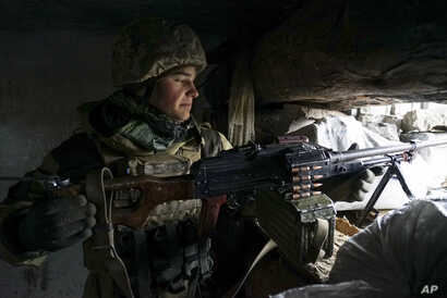A Ukrainian soldier takes his position near the frontline with Russia-backed separatists, in Shyrokyne, eastern Ukraine, Nov. 28, 2018.