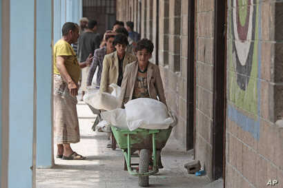 Displaced Yemenis receive food supplies provided by the World Food Program, at a school in Sana'a, Aug. 25, 2019.