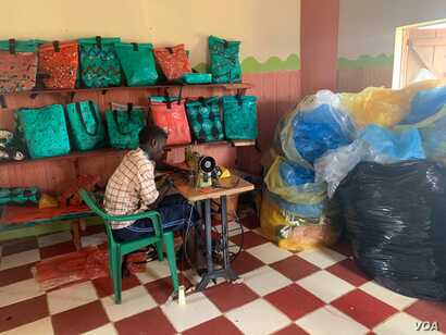 A tailor sits next to a display shelf in the Reform Africa workshop, in Mpigi district, Uganda. (H.Athumani/VOA)