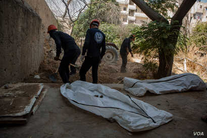 Employees of Raqqa's Civil Defense dig in a garden looking for corpses of IS fighters and their families in Raqqa, Syria, Sept.