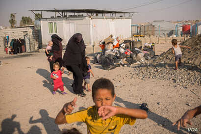 Women in the Ain Issa Camp carry their children, while boys play, in an area set aside for foreigners who came from all over the world to join IS, Sept. 1, 2019. (Yan Boechat/VOA)
