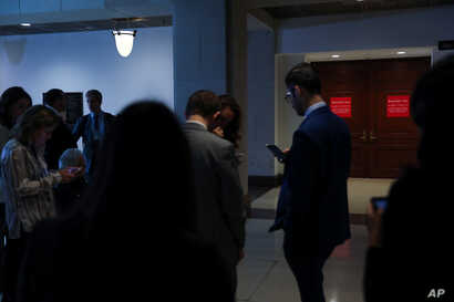Reporters wait outside of closed U.S. House Intelligence Committee rooms while Intelligence Community Inspector General Michael Atkinson testifies on a whistleblower complaint, on Capitol Hill, in Washington, Sept. 19, 2019.