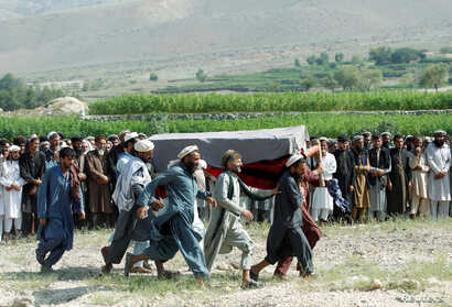 FILE -  Men carry a coffin of one of the victims after a drone strike, in Khogyani district of Nangarhar province, Afghanistan, Sept. 19, 2019.