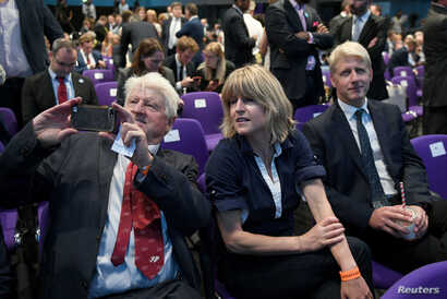 FILE - Stanley, Rachel and Jo Johnson, Boris Johnson's father, sister and brother, wait for the announcement that he has been elected leader of the Conservative party, at the Queen Elizabeth II Centre in London, July 23, 2019.