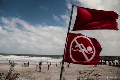 Red flags to indicate that the ocean has a high tide and locals should not be swimming due to danger are seen at Jacksonville Beach before Hurricane Dorian, in Jacksonville, Florida, Sept. 3, 2019.