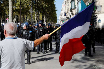 A protester holds a French flag as he takes part in a demonstration on Act 45 (the 45th consecutive national protest on Saturday) of the yellow vests movement in Paris, France, Sept. 21, 2019.