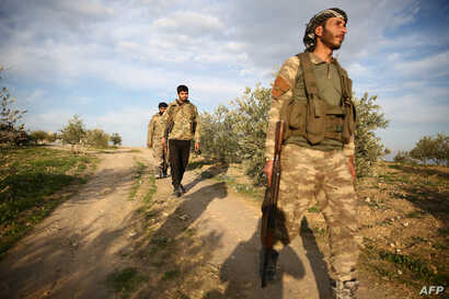 Turkey-backed Syrian fighters walk down a road in the town of Qirata, near the rebel-held border town of Jarabulus, on December…