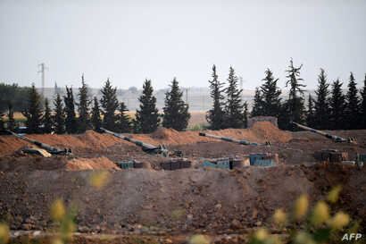 This picture shows artillery pieces on the Turkish side of the border with Syria near Akcakale in Sanliurfa province on October…