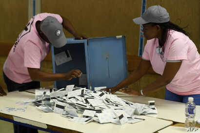 Polling officers verify ballots from ballot boxes arriving at a counting centre in the Ledumang Senior Secondary school for the…