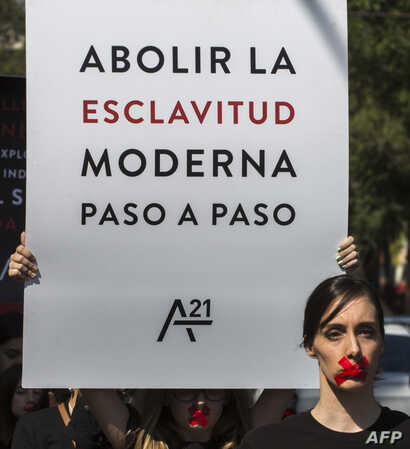 "A woman holds a poster reading ""Abolish modern slavery step by step"" as she joins hundreds wearing black shirts and bearing red…"
