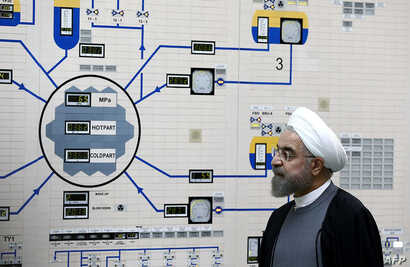 A handout picture released by the official website of the Iranian President Hassan Rouhani, shows him visiting the control room…