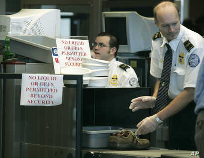 FILE - Transportation Security Administration (TSA) workers screen passenger belongings at a security checkpoint at Washington Dulles International Airport in Chantilly, Virginia.