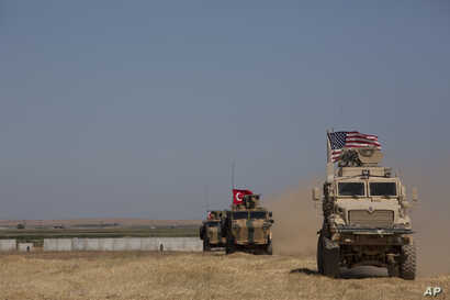 "Turkish and American forces conduct their first joint ground patrol in the so-called ""safe zone"" on the Syrian side of the…"