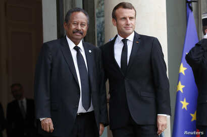 France's President Emmanuel Macron, right, welcomes Sudanese Prime Minister Abdalla Hamdok prior to a meeting at the Elysee palace in Paris,  Sept. 30, 2019.