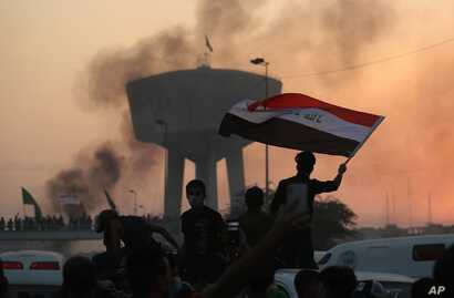 Anti-government protesters wave flags during a demonstration in Baghdad, Iraq, Oct. 2, 2019.