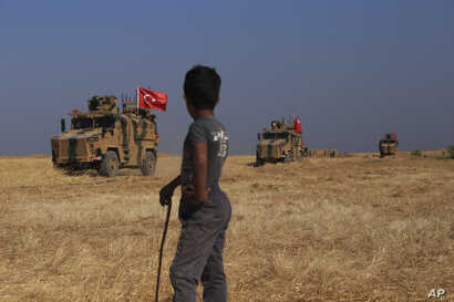 """A Turkish armored vehicles patrol joins a joint ground patrol with American forces in the so-called """"safe zone"""" on the Syrian side of the border with Turkey, Oct.4, 2019."""