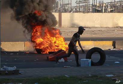 Anti-government protesters set fires and close a street during a demonstration in Baghdad, Iraq, Friday, Oct. 4, 2019. Security…