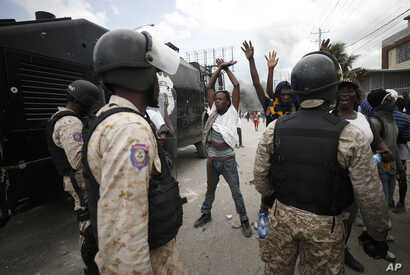 Protestors calling for the resignation of President Jovenel Moise raise their arms in front of a group of police in riot gear,…
