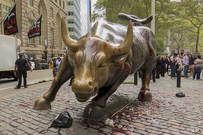 """In this freeze frame made from a video stage blood covers the iconic """"Charging Bull"""" statue near Wall Street on Monday Oct. 7,…"""