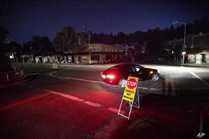 A car drives through a darkened Montclair Village as Pacific Gas &  Electric power shutdowns continue in Oakland, Calif. The…
