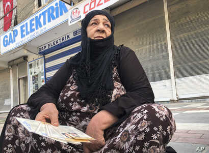 Soufida Gedou, 65, a Syrian refugee living in Akcakale, southeastern Turkey, waits for bread distribution by the local…