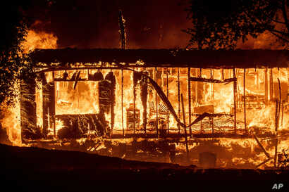 Flames consume a home as the Kincade Fire tears through the Jimtown community of Sonoma County, Calif., on Thursday, Oct. 24,…