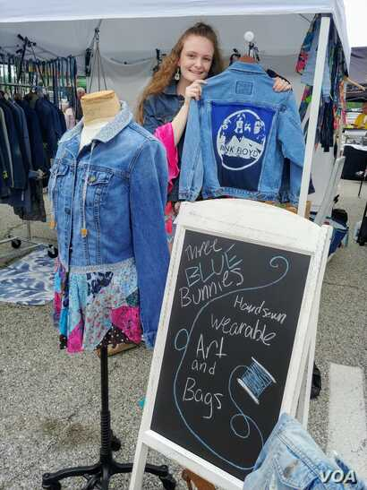 Ellie Heath stands next to some of her designs - repurposed jeans jackets adorned with her distinctive artistic touch (Photo: F. Elmasry / VOA)