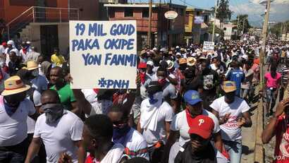 """Haiti police protest in Port au Prince, Sunday, Oct 27, 2019. Poster says """"19,000 (about 1,900 US dollars) Gourdes cannot support a family."""