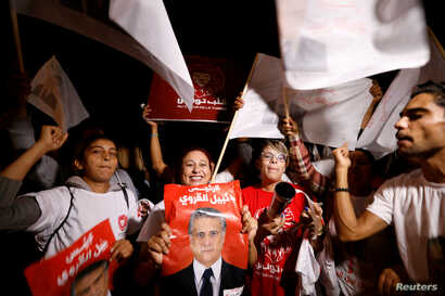 Supporters of Tunisian presidential candidate Nabil Karoui celebrate after he was freed, days before Sunday's second-round…