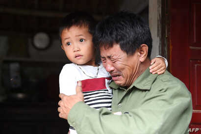 Le Minh Tuan, father of 30-year old Le Van Ha, who is feared to be among the 39 people found dead in a truck in Britain, cries while holding Ha's son outside their house in Vietnam's Nghe An province.