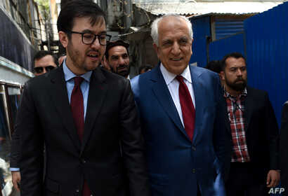 FILE - U.S. special representative for Afghan peace and reconciliation Zalmay Khalilzad (R) arrives for a forum talk at Tolo TV, in Kabul, Afghanistan, April 28, 2019.